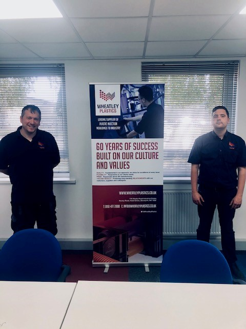 Employees Gary and Adam with promotional roll up banner